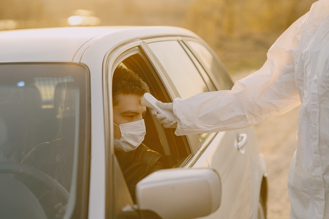Man getting his temperature taken while in his car by a healthcare professional wearing personal protective equipment (PPE)